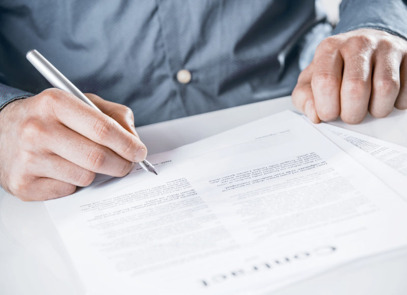 Businessman signing a legal document with text with a silver fountain pen, close up of his hands as he sits at a desk